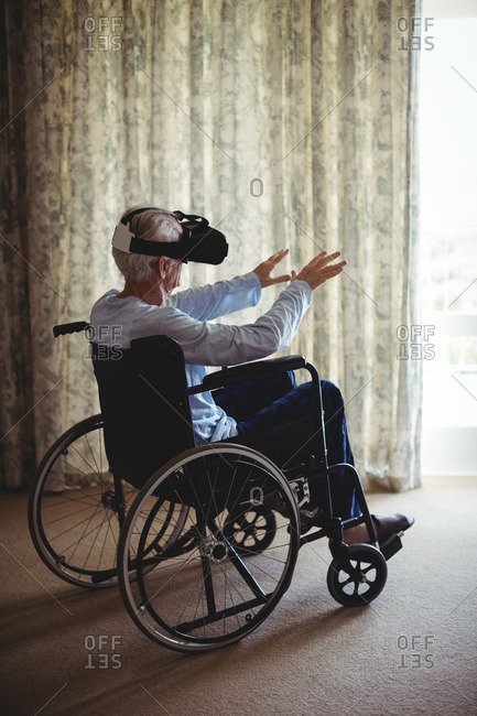 Senior man sitting on wheelchair and using virtual reality headset in bedroom at home