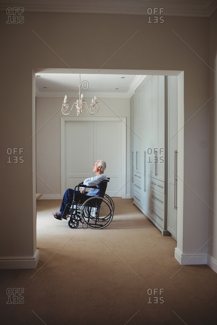 Senior man sitting on wheelchair and using virtual reality headset at home