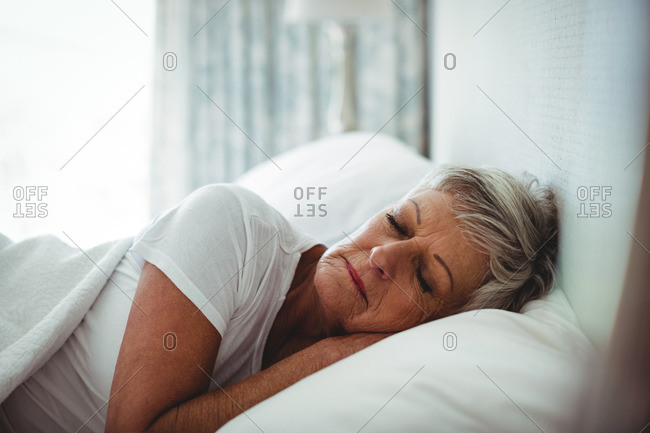 Senior woman resting on bed in bedroom at home