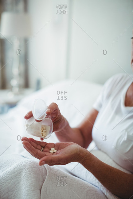Mid section of senior woman taking medicine in bedroom at home