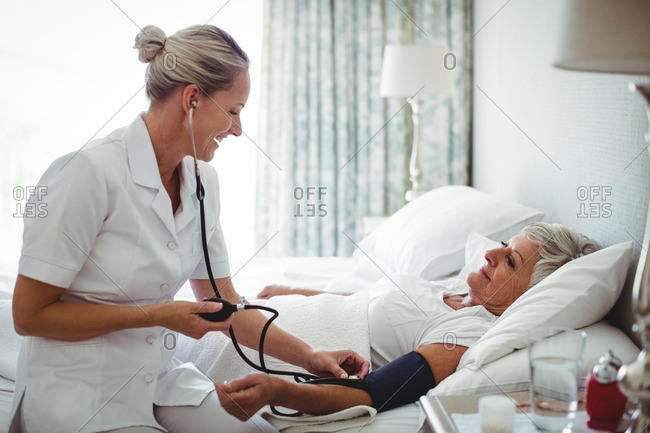 Nurse checking blood pressure of senior woman at home