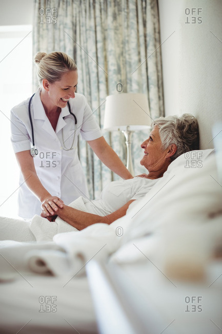 Female doctor interacting with senior patient at home