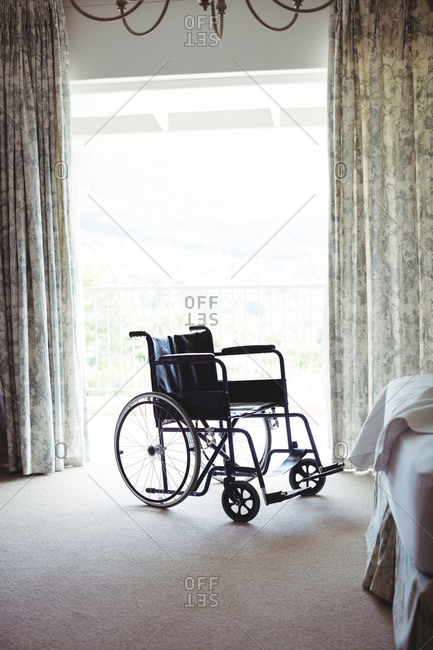 Empty wheelchair in bedroom at home