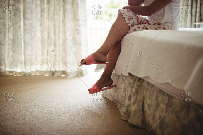 Low section of senior woman sitting on bed in bedroom