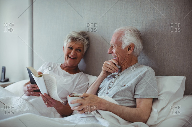 Senior man having breakfast while woman reading a book on bed in bed room