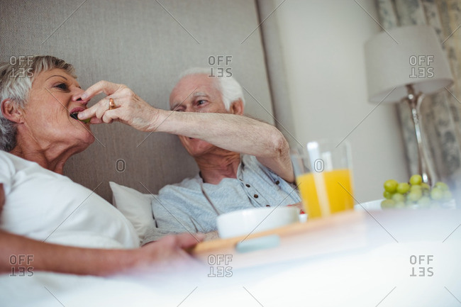Senior couple having breakfast on bed in bed room