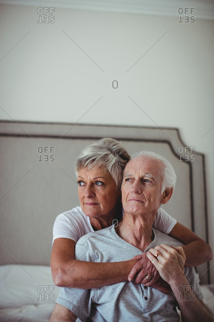 Senior woman embracing senior man on bed in bed room