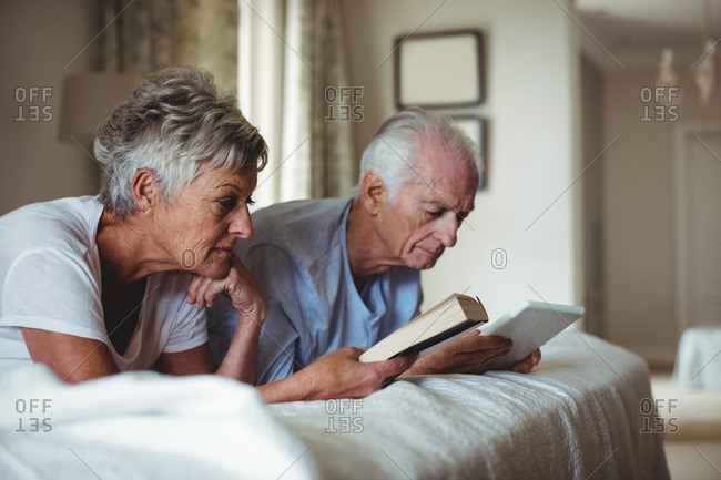 Senior woman reading a book and senior man looking at digital tablet on bed in bed room