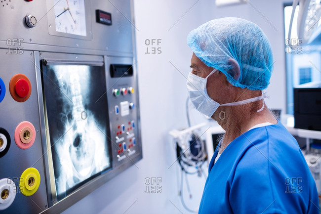 Male surgeon reading x-ray in operation theater