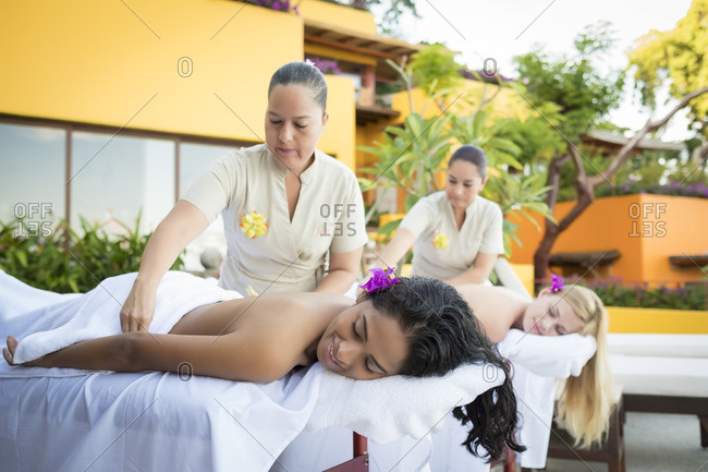 Two young women receiving a massage at a luxury vacation retreat