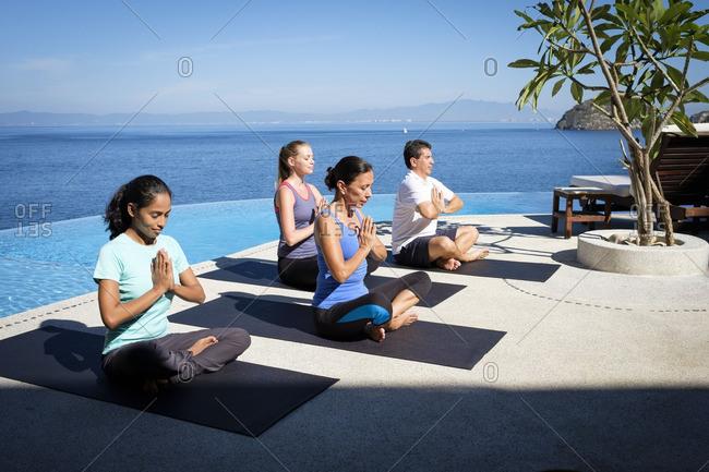Yoga group exercising at ocean front resort