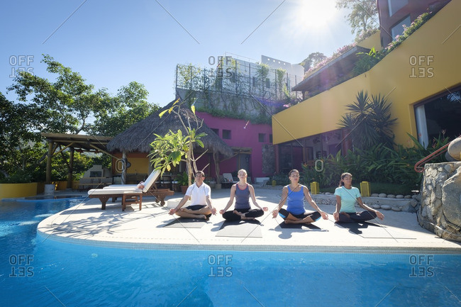 Yoga group exercising at ocean front villa