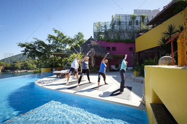 Yoga group exercising at ocean front villa