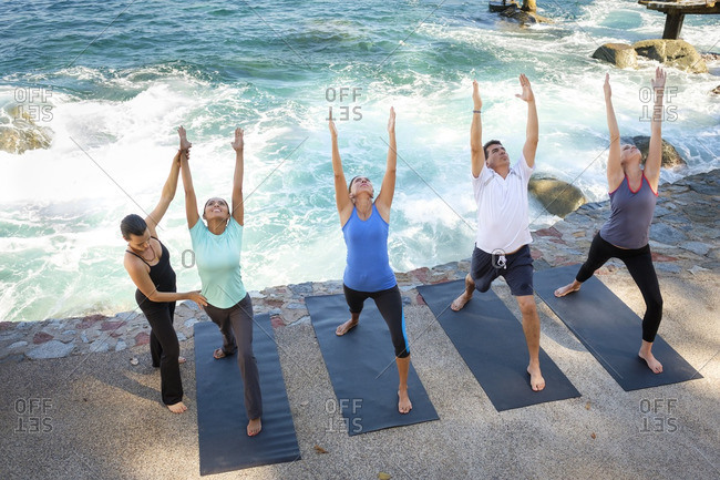 Instructor helping group doing yoga at ocean front