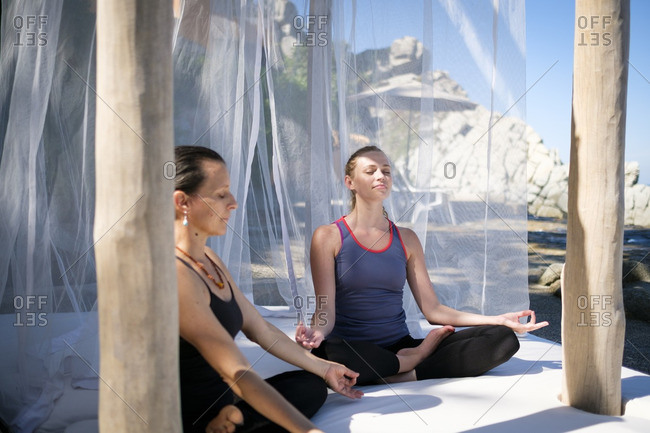 Two women practicing yoga meditation in a cabana