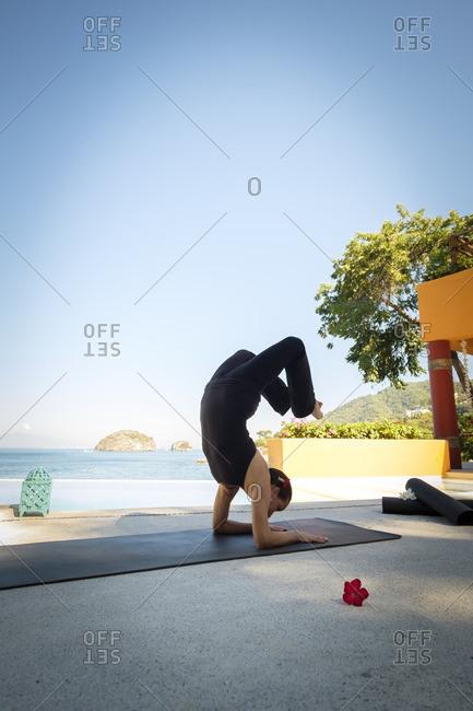 Woman practicing yoga at ocean front resort