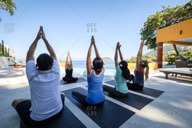 Yoga group with teacher exercising at ocean front villa