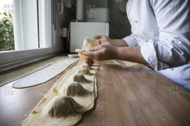 Man preparing handmade raviolis in kitchen