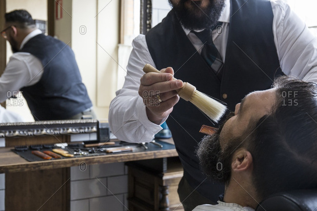 Barber cleaning the beard of a man with a brush