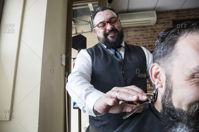 Barber cutting the hair of a man using a vintage hand operated hair clipper