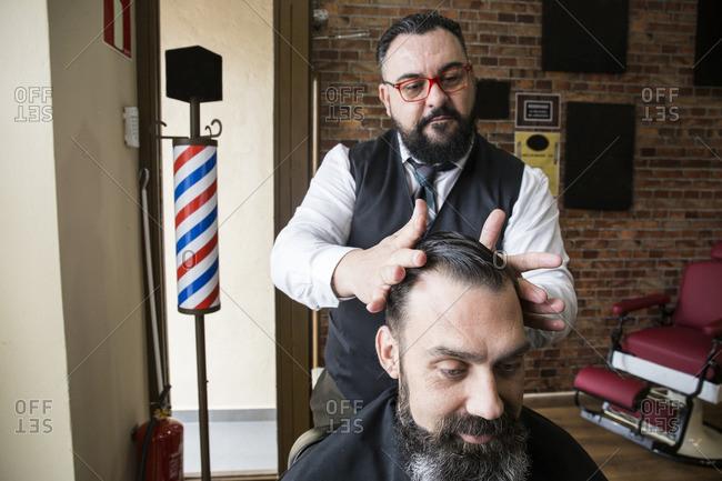 Barber checking the haircut of a man