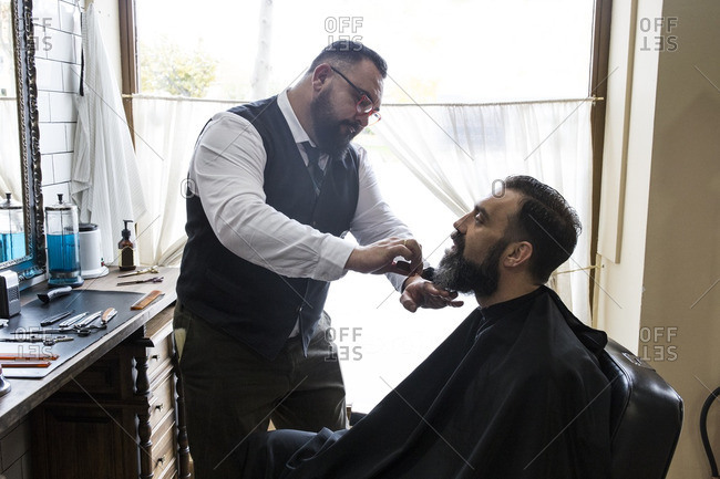 Barber brushing the beard of a man with a hair brush