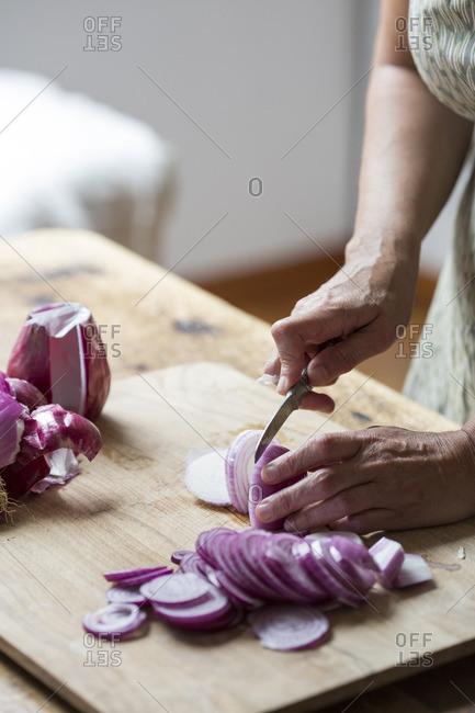 Woman preparing red onions for onion pesto