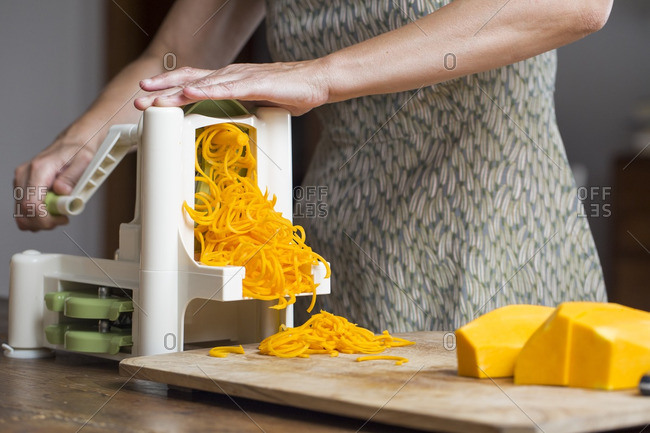 Woman preaparing pumpkin noodles in spiral vegetable slicer