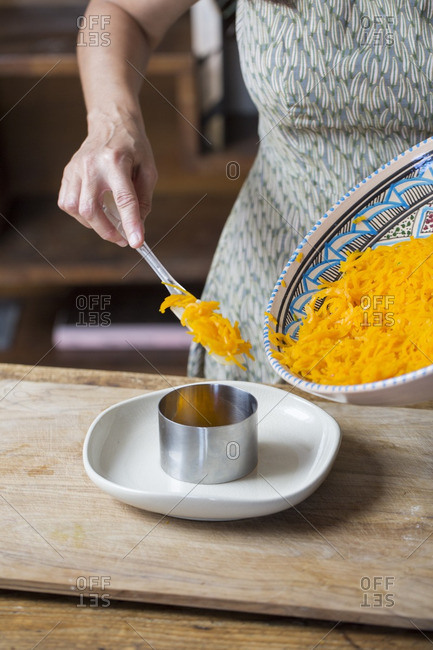 Woman arranging raw pumpkin noodles and onion pesto on plate