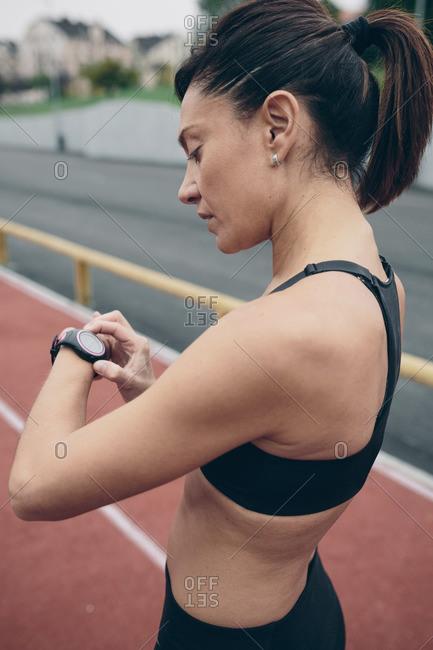 Athlete on tartan track looking on smart watch