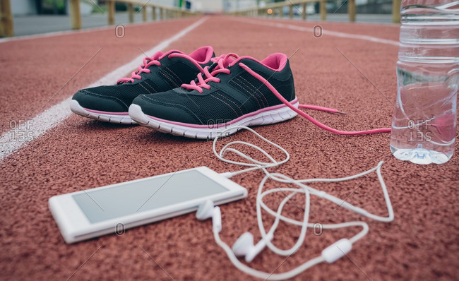 Sport shoes- smartphone with earbuds and bottle of water on tartan track