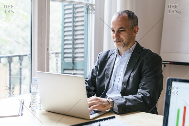 Businessman sitting at desk working on laptop