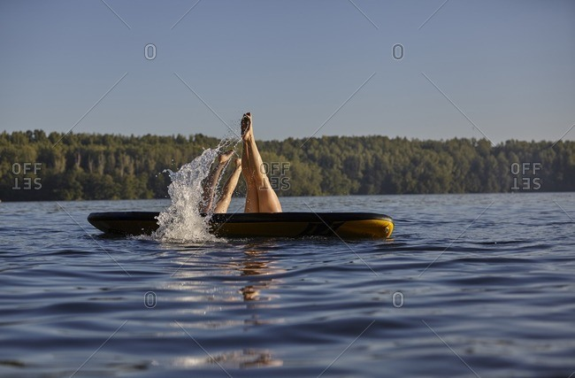 Two women jumping into water from paddleboard