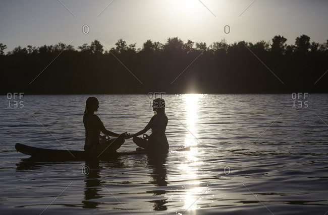 Two women doing yoga on paddleboard at sunset