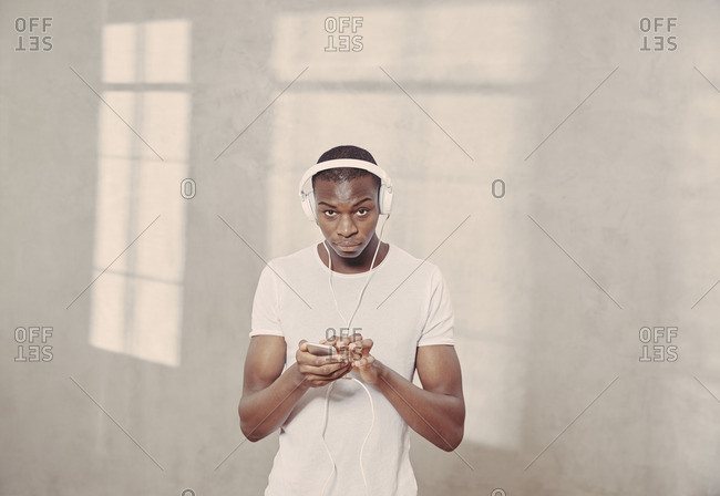 Portrait of young man listening music with headphones and cell phone
