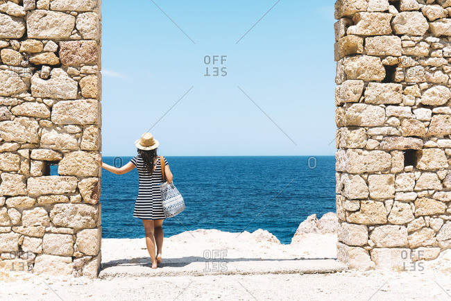 Firopotamos Beach- Woman standing in door in stone wall- looking at distance