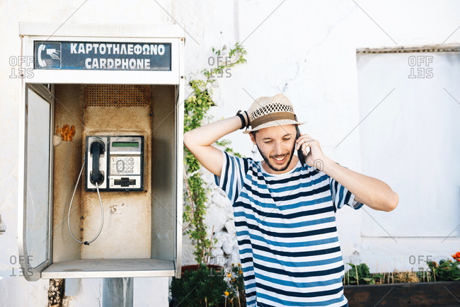 Klima- Man talking on cell phone- leaning against old telephone booth
