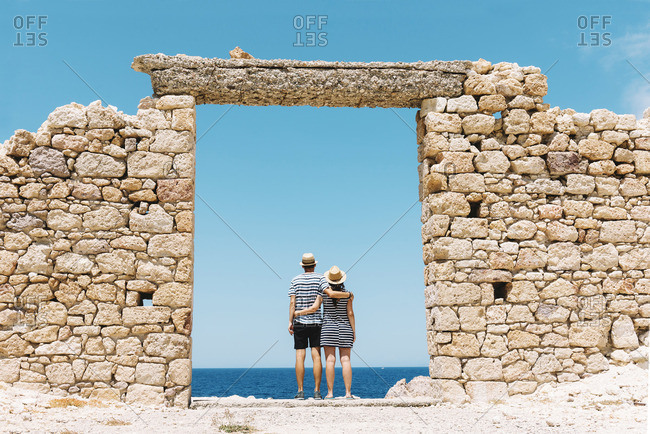 Firopotamos Beach- Couple standing in door in stone wall- looking at distance