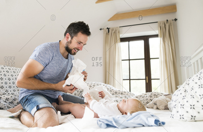Father changing baby's diapers on bed