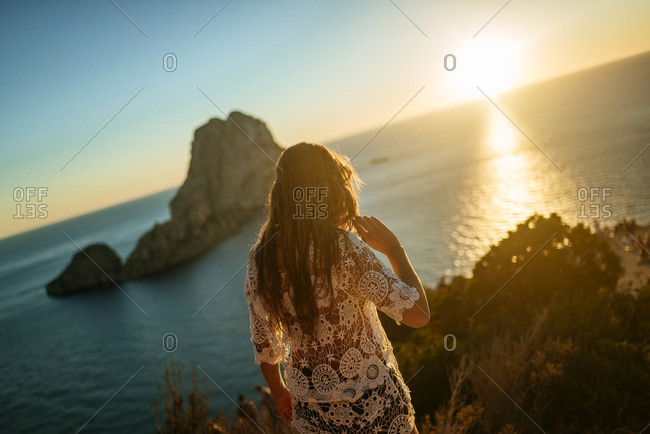 Spain- Ibiza- Woman looking at the sea and Es Vedra island at sunset