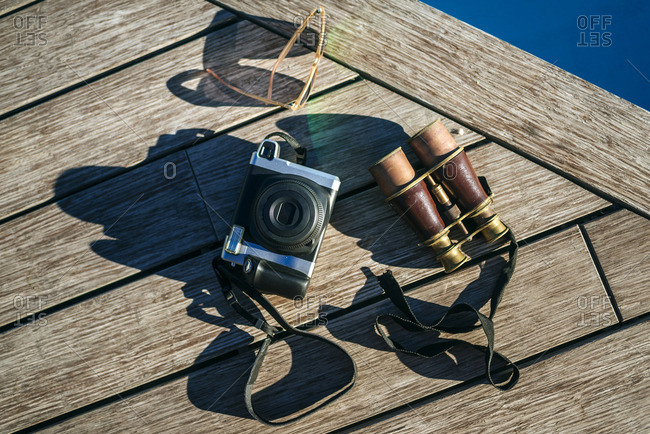 Binoculars- camera and sunglasses on wood
