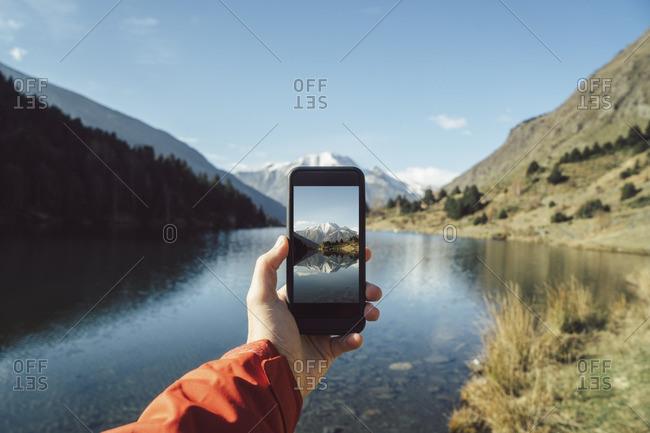 Man taking a picture at mountain lake