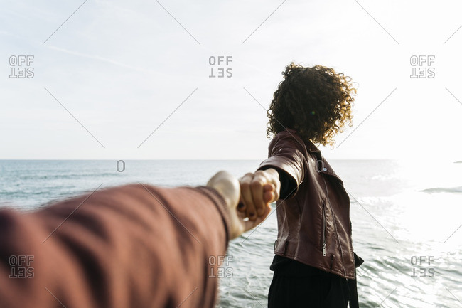 Woman in front of the sea holding hand with her friend