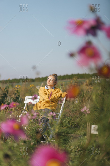 Young woman relaxing in cottage garden