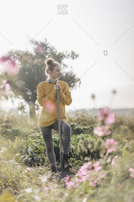 Young woman with spade in cottage garden