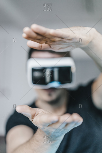Man with raised hands wearing VR glasses