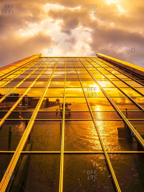 Harbor reflecting on modern facade at sunset