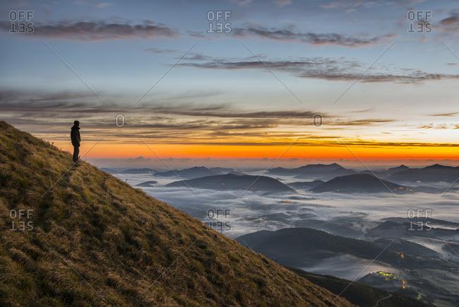 Hiker  standing on Monte Acuto watching sunrise