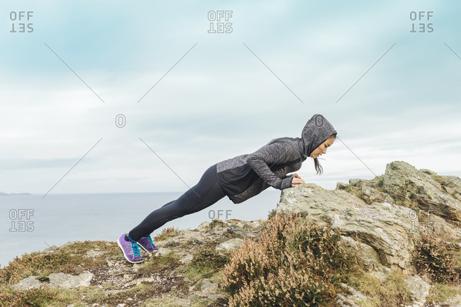 Woman exercising at cliff coast