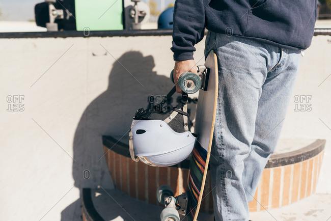 Man in a skatepark holding skateboard and helmet